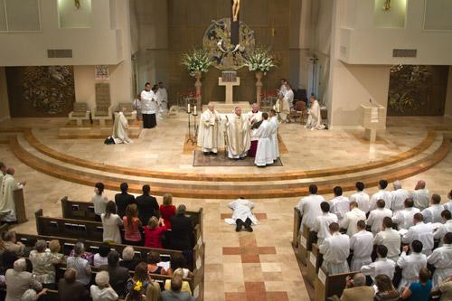 During the Litany of Supplication, Father George Sanders lays prostrate before the altar at Christ the King Church in Little Rock during his ordination Mass. Also on the front rows were most of the 41 seminarians who are preparing to return to school later this month. Bob Ocken photo