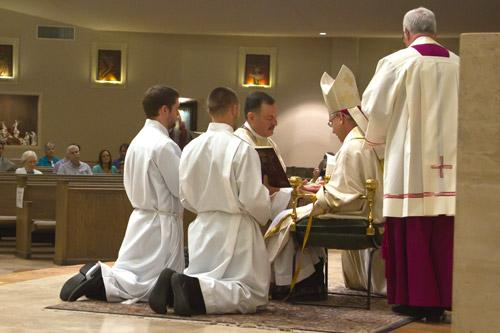 After being invested with a stole and chasuble, Father George Sanders kneels before the bishop who anoints his hands with chrism oil. Bob Ocken photo