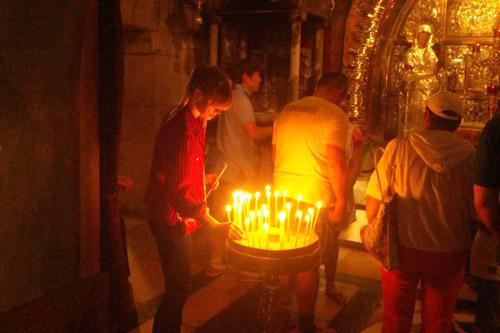 Hebda lights a candle at the Church of the Holy Sepulchre in Jerusalem, site of the crucifixion of Jesus.