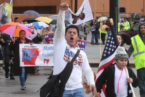 Nelson Escobar leads the walk across Walnut Avenue in Rogers Oct. 5 during a downtown march to support immigration reform. Gerard Davenport photo