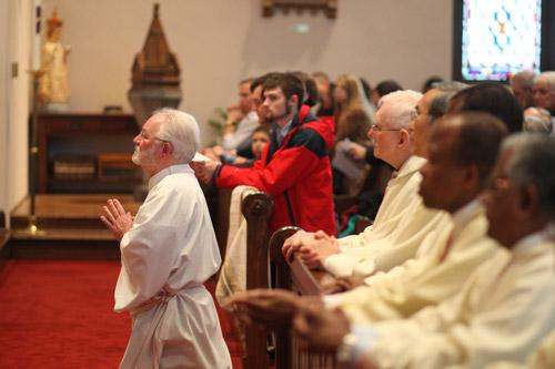 Jack Sidler Sr. kneels before the bishop during his diaconate ordination Mass at St. Boniface Church in Fort Smith.