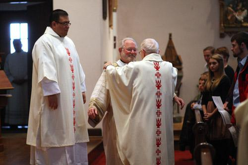 Pastor Father Henry Mischkowiuski helps Deacon Jack Sidler put on his stole and dalmatic. Deacon Juan Guido (left) looks on.