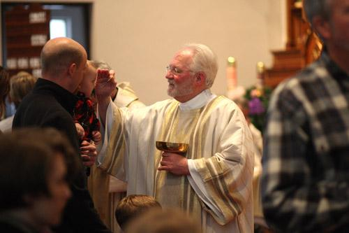 Deacon Jack Sidler blesses a child before distributing Communion.