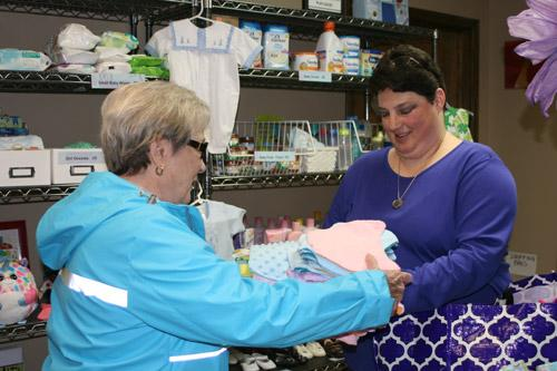 "Melissa Ziegenhorn is known as the ""Blanket Lady"" at Arkansas Pregnancy Resource Center. She's seen here handing off blankets to center volunteer Joan Wehr. (Aprille Hanson)"
