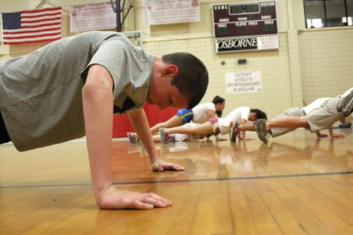 Seventh-grade fitness team member Dylan Moss pumps out a few more pushups before the clock runs out. Many participants balance fitness training with other sports.  (Dwain Hebda photo)