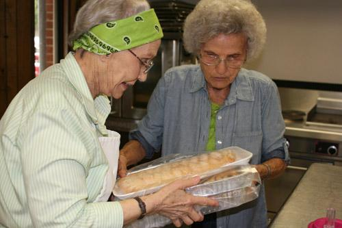 "Roberta Uhiren (left), dubbed ""Mother Superior"" by the Slovak Bakers, hands off baked goods to Francis Chudy, the oldest member at 89 years old. (Aprille Hanson photo)"
