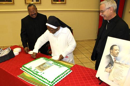 At a dinner following Mass, Sister de Porres cuts Dr. King's birthday cake under the gaze of Father Warren Harvey (left) and Bishop Anthony B. Taylor. (Dwain Hebda photo)