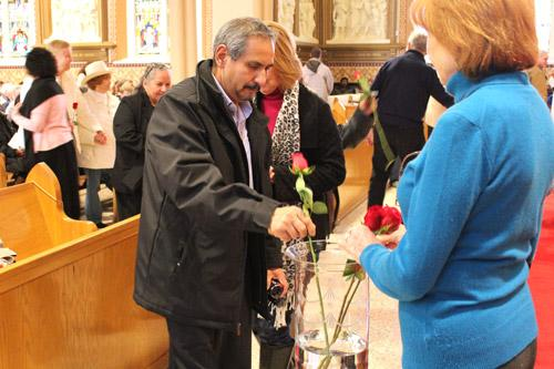 A man places a rose in a vase during the offertory. Individuals who had lost a child for any reason were given a rose and asked to bring it up as a remembrance. (Dwain Hebda photo)