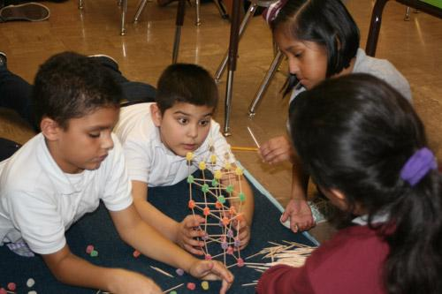 Throughout the classroom, few towers looked alike, each figuring out different shapes and ways to build it. Pictured are: Mathew Angeles, third grade (left); Jose Gutierrez, second grade; Mackenzie Delgado, third grade; and Isabela Ruiz, third grade. (Aprille Hanson photo)
