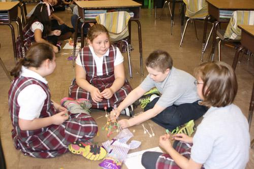 Second grader Andrew Gangluff works on building the tower while his group discusses their design. Others pictured are: Olivia Sutton, third grade (left); Sheyla Green, third grade; and Anna Williams, fourth grade. (Aprille Hanson photo)