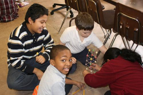 Second grader Patrick Mays flashes a smile at the camera, enjoying the latest STEM project. Others pictured are: Gabriel deLuna Vargas, third grade; Jack Moritz, fourth grade; and Isabella Martinez fourth grade. (Aprille Hanson photo)
