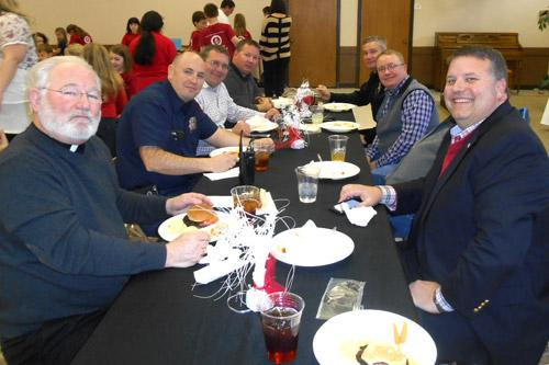 Father Jack Sidler (front left) sits with parents, staff and community leaders during the annual VIP Lunch at St. John School in Russellville to conclude Catholic Schools Week. The school also honored local police officers, priests and nuns. (Print not available for this photo.)