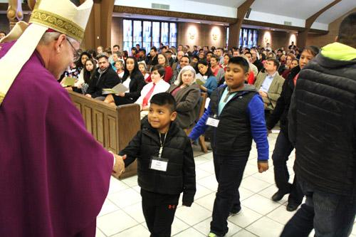Bishop Anthony B. Taylor shakes a young catechumen's hand during the Feb. 14 celebration of the Rite of Election for central Arkansas. (Dwain Hebda photo)