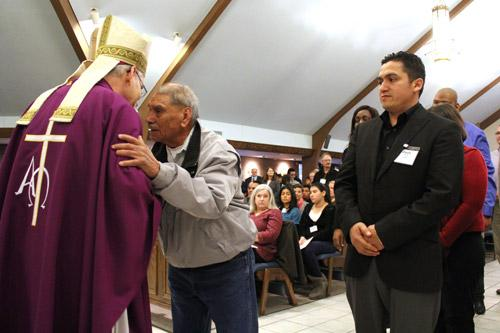 An older man whispers to Bishop Taylor after shaking the man's hand during Rite of Election ceremonies Feb. 14. (Dwain Hebda photo)
