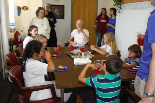 The Little Flowers Girls Club from St. Andrew Church in Ratcliff went to Subiaco Abbey's infirmary, visiting with Sister Judith Weaver (back left), a diocesan hermit, Brother Andrew Suarez (back, standing) and the late Brother Eric Loran (seated, center).