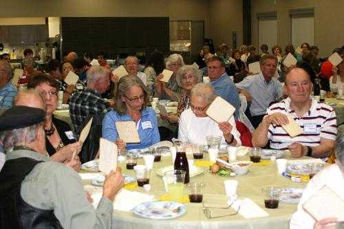 St. Mary of the Springs parishioners hold up their Matzo (unleavened bread) during the Seder meal March 10. (Aprille Hanson photo)