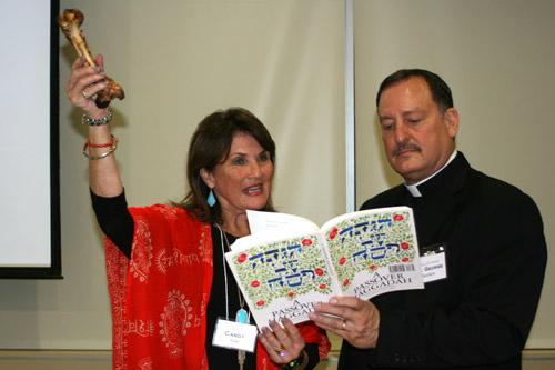 St. Mary parishioner Candy Kaler, a Catholic who studied with RCIA this year, holds up a Z'roa (a lamb shank) as part of the Seder meal, while reading along with Father George Sanders. (Aprille Hanson photo)