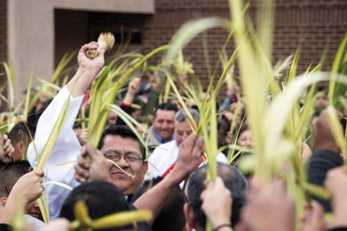 Seminarian Deacon Mario Jacobo blesses the palms outside before Mass at St. Raphael Church in Springdale on Palm Sunday March 20. (Travis McAfee photo)