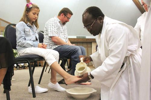 Pastor Father John Wakube, AJ, washes the feet of second-grader Anna Dearworth during Holy Thursday Mass at Immaculate Conception Church in North Little Rock. Anna was one of 12 people to have their feet washed. (Dwain Hebda photo)