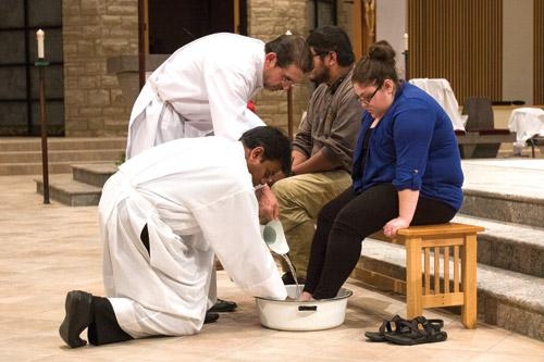 At St. Vincent de Paul Church in Rogers on Holy Thursday, associate pastor Father John Miranda assisted by Deacon Sylvestre Duran washes the feet of Carolyn Lawson after just finishing washing the feet of Josh Smith. (Paul Dufford photo)