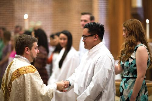 Administrator Father Andrew Hart shakes hands with Daniel Sundara during the Easter Vigil Mass at St. Thomas Aquinas University Parish in Fayetteville. Sundara, who grew up Buddhist, came into the Church through the support of his wife, Kelsey, who was also his sponsor. (Travis McAfee photo)