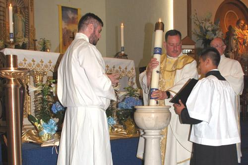 Seminarian Luke Womack looks on as pastor Father George Sanders lowers the paschal candle into the water three times during the Easter Vigil at St. Mary Church in Hot Springs.  Altar Server Dylan Nguyen holds the Missal. (Prints not available.)