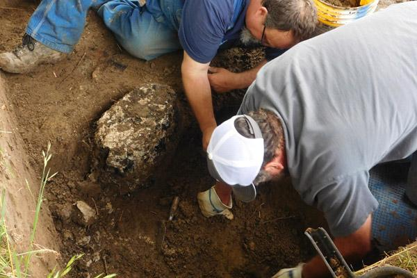 Archaeologists Jared Pedworth (left) and Mike Evans work to remove the charred remains of what they believe could be a 475-year-old cross Tuesday, April 19. The wood is currently being testing through radiocarbon dating and tree ring analysis. (Jessica Crawford photo, The Archaeological Conservancy)