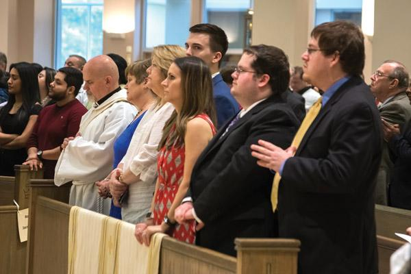 Norman McFall, his wife Laura, their son Samuel (second from right), family and friends listen to the bishop at the beginning of the ordination Mass. McFall was ordained through a special provision from the Vatican. (Bob Ocken photo)