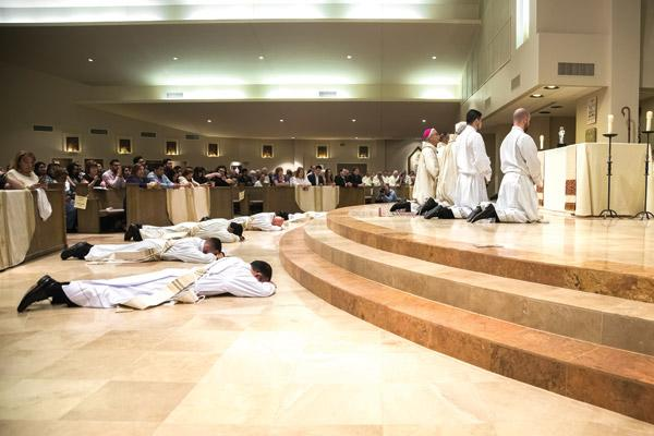 Five candidates for priesthood prostrate themselves in an act of surrender before God while the congregation sings the litany of the saints. (Bob Ocken photo)