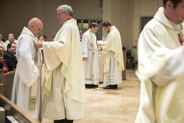Father Andrew Smith helps Father McFall (left) vest while Father Ruben Quinteros helps Father Whittington vest with the stole and chasuble during their ordination Mass. (Bob Ocken photo)