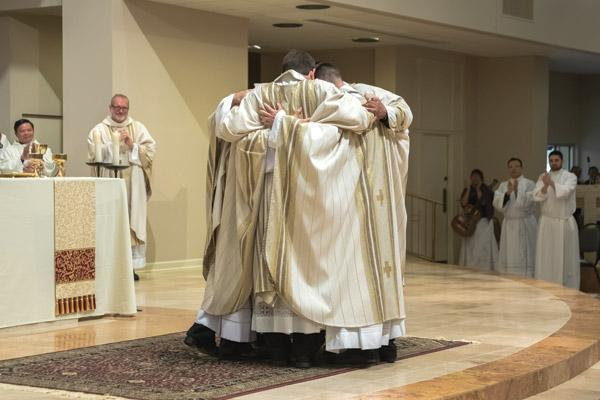 After receiving the sign of peace from the bishop and their brother priests, the five new priests for the diocese embrace each other while onlookers applaud. (Bob Ocken photo)