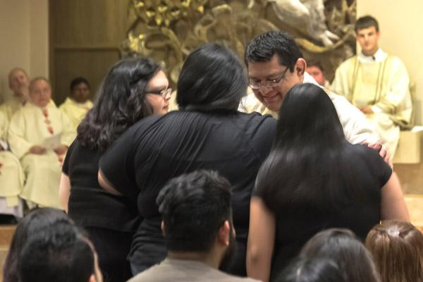 Newly ordained Father Mario Jacobo blesses members of his family from Georgia during the ordination Mass. (Bob Ocken photo)