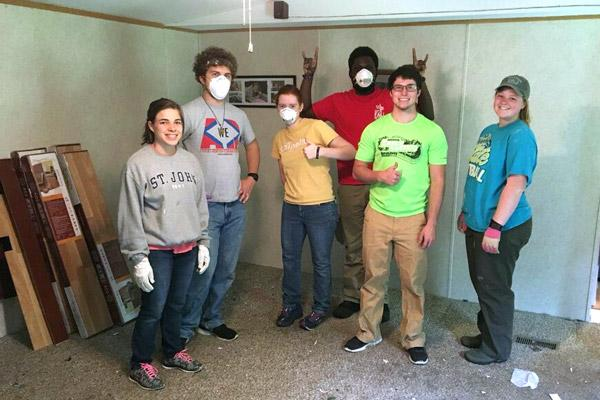 Students help lay flooring in the home of a low-income family in Appalachia during a May mission trip. Pictured are Holly Hambuchen (left), Sam Johnson, Clare Doss, Anthony Bassey, Blake Marshall and Morgan Burke.