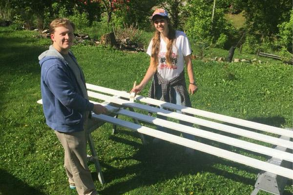 Students Nick Baltz and Katie Karp help paint a fence outside a home in Chavies, Ky. A $20,000 grant was given to the diocese by Catholic Home Missions to sponsor a mission trip for college students during the Year of Mercy.