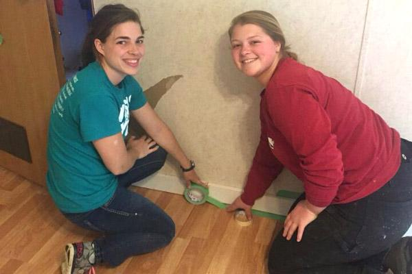 Holly Hambuchen (left) and Morgan Burke prepare to paint the trim inside a home in need of repair.