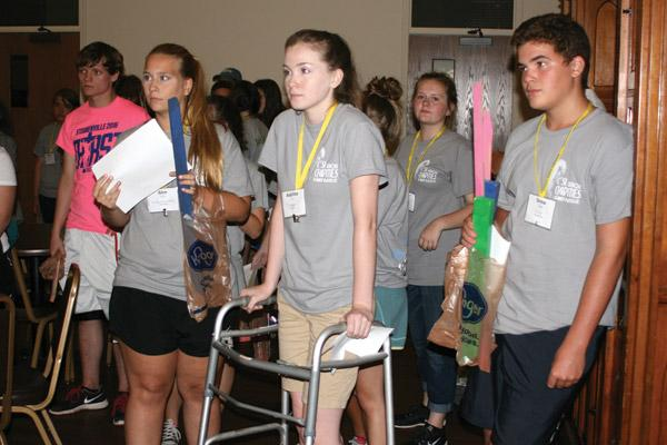 "With only their allotted ""supplies"" and assigned character for the journey, Allee Haynes, 18, of Our Lady of the Assumption in Booneville (front, left), Avanlea Furr, 17, of St. Agnes in Mena and Drew Capps, 14, of St. Paul in Pocahontas, prepare to set out toward hoped-for safety. (Aprille Hanson photo)"