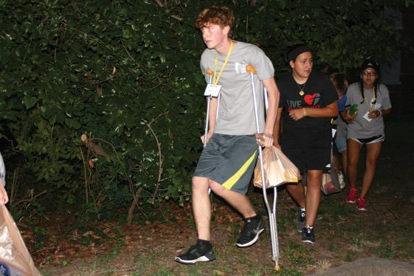Andrew Eveld, 16, of Sacred Heart Church in Charleston, stumbles over rough ground on the crutches needed by his assigned character as he avoids the pavement and a chance of capture, followed by Nicole Salman, 18, of St. James Church in Searcy and Jasmine Rico, 17, of St. Edward Church in Little Rock. (Aprille Hanson photo)