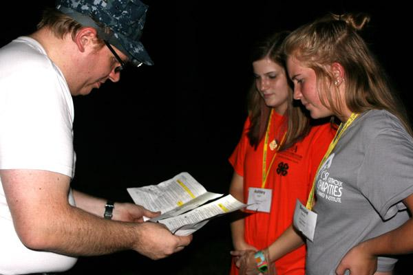 """Border patrol official"" Jeff Heeter, of Christ the King Church in Little Rock, examines the paperwork of Ashley Beyer, 18 (center), of St. Michael Church in West Memphis and Bessie Sullivan, 16, of St. Stephen Church in Bentonville, before letting them cross into ""Mexico."" (Aprille Hanson photo)"