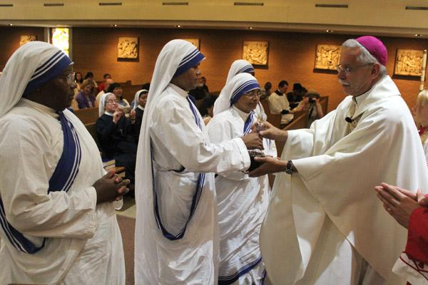 Sister Maria Jyoti hands Bishop Anthony B. Taylor the decanter of wine flanked by her fellow Missionaries of Charity Sisters during Mass for St. Teresa of Kolkata Sept. 4. (Dwain Hebda photo)