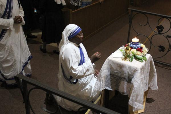 Sister Marie Jose kneels before St. Teresa's relics following Mass. St. Teresa had been canonized by Pope Francis the previous day. (Dwain Hebda photo)