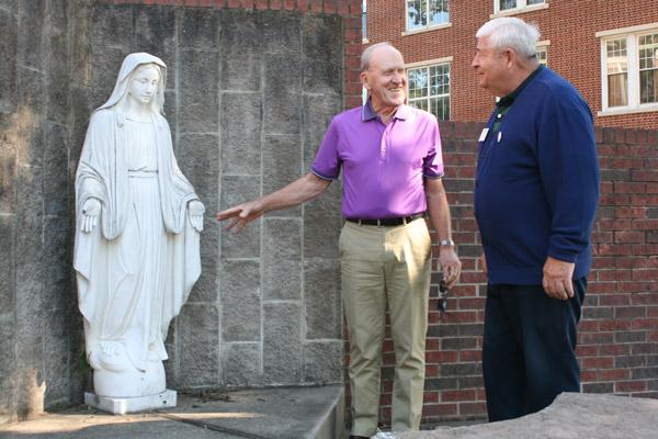 Knights of Columbus member Bob Honzik (left) and grand knight Tom Donnelly, from Sacred Heart of Jesus Church in Hot Springs Village, discuss the damage to the Virgin Mary statue Oct. 11. (Aprille Hanson photo)