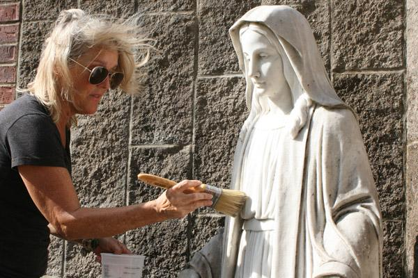 Michele Bowman brushes cleaner onto the Virgin Mary statue. While she did not have the exact cleaning supplies needed for carrara marble on hand, she was able to make the marble shine brighter than before. (Aprille Hanson photo)