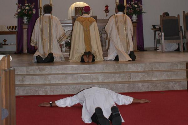Nelson Rubio prostrates himself during the litany of saints at his diaconate ordination Dec. 17 while Bishop Anthony B. Taylor and Deacons Martin Siebold (left) and Ramses Mendieta pray. (Aprille Hanson photo)