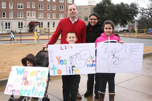 Adam and Marcela Stengel and their three children, members of St. Anthony Church in Ratcliff, display their homemade signs for the March for Life in Little Rock. (Malea Hargett photo)