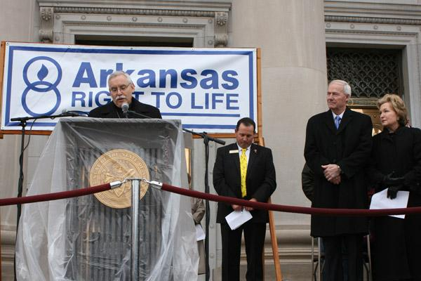 Bishop Anthony B. Taylor prays at the start of the March for Life program on the State Capitol steps. Gov. Asa Hutchinson and First Lady Susan Hutchinson and Rep. Andy Mayberry, president of Arkansas Right to Life, listen. (Malea Hargett photo)