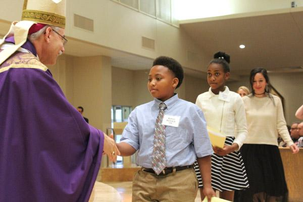 Rodney Nichols Jr. shakes Bishop Taylor's hand during the Rite of Election. Nichols is a catechumen at Immaculate Heart of Mary Church in North Little Rock (Marche)  (Dwain Hebda photo)