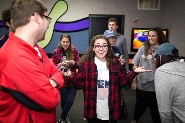 Christa Murad jokes with her friends from St. Thomas Aquinas University Parish in Fayetteville during a March 2 group outing to Ozark Lanes for bowling and fellowship. (Travis McAfee photo)