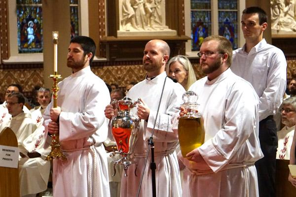 Seminarians Jon Miskin, Patrick Friend and Keith Higginbotham present the oil of catechumen during the Chrism Mass April 10 at the Cathedral of St. Andrew. The holy oils used during the year in all parishes are blessed by the bishop at this annual Mass. Priests also recommit to priestly service during the Mass. (Malea Hargett photo)
