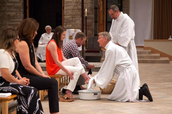 Msgr. David LeSieur, pastor of St. Vincent de Paul Church in Rogers, is assisted by Deacon Ronnie Hoyt in washing the feet of Madeline Marks at Holy Thursday Mass April 13. Also having their feet washed are Marta Orellano (left), Elda Scott and James Ryan. (Paul Dufford photo)