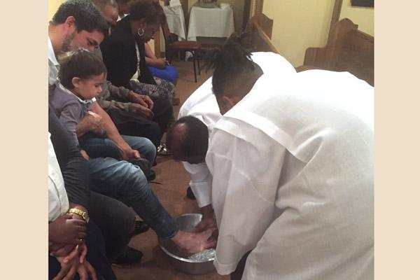 Father Francis Damoah, pastor at St. Augustine Church in North Little Rock, washes St. Bartholomew parishioner Adelso Martinez Peña's feet on Holy Thursday while his young son Emmanuel Martinez Peña watches. (Courtesy St. Augustine Church) Prints not available for this photo.